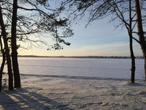 Frostat vintersjölandskap för solnedgång arkivfoton