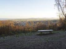 Frosted ławka przegapia miasteczko otaczającego wsią z górzystym tłem, Brytyjska wioska urocza Zdjęcia Royalty Free
