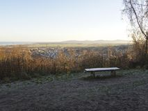 Frosted bench overlooking Small town surrounded by countryside with mountainous background, British Village quaint royalty free stock photos