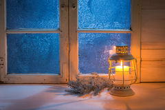 Frosted blue window with burning candle for Christmas at night. On old white table Royalty Free Stock Photos