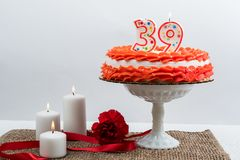 Frosted cake with 39 candle. Red and white frosted cake with 39 candle on top for a 39th anniversary or birthday.  Three candles and a carnation and ribbon Stock Image