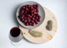 Frosted cherries, glass of red wine, rosemary and thyme stock image