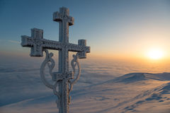 Frosted cross and sunrise scene in mountains Stock Photos