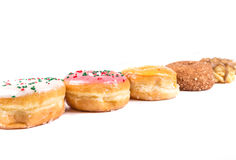 Frosted donut lineup. Shallow depth of field isolated on a white background Royalty Free Stock Images