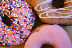 Frosted donuts with pink frosting and multi colored sprinkles Royalty Free Stock Photos