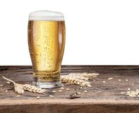 Frosted glass of beer on the wooden table. Stock Photo