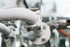 The frosted industrial refrigeration compressor pipeline. Frozen ball valve Stock Photos