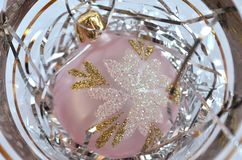 Frosted light pink Christmas ball decoration on a bed of silver hair in a clear background. Close up. Flat layout Royalty Free Stock Photos