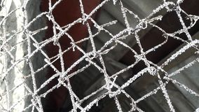 Icy, frosted spider webs on wire fence. Dark background stock images