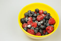Frosted raspberries and blueberries in a bowl, isolated on white. Frosted fruits of highbush bluberyy and raspberries in yellow bowl isolated on white background Royalty Free Stock Photo