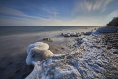 Frosted stones on the sea shore Stock Photography