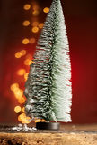 Frosted toy Christmas tree with party lights. Frosted tall conical green toy Christmas tree with a sparkling bokeh of festive orange party lights behind on a Royalty Free Stock Image
