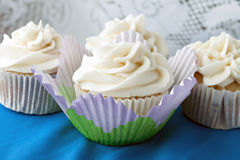 Frosted Vanilla Cupcakes. Close up of some decadent gourmet cupcakes with vanilla frosting stock image