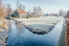 Frosted water in a canal in Zaanse Schans, Netherlands. Winter scenary with frosted canal and traditional wood house in Zaanse Schans, Netherlands Stock Photography
