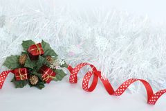 frosted white wreath with red ribbon and green leaves, red gifts on white background for party decoration Royalty Free Stock Photo