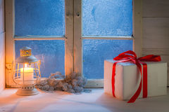 Frosted window with burning candle for Christmas at night Royalty Free Stock Photos