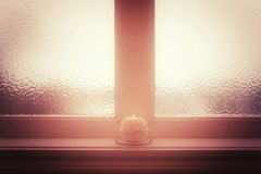 Frosted window and burning candle and in misty light. Winter mood Royalty Free Stock Photography