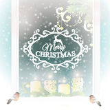 Frosted window with Christmas decoration. Royalty Free Stock Photo