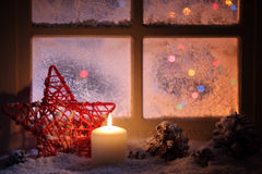 Frosted window with festive candles. And holiday decorations Stock Images