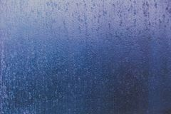 Frosted window glass with ice texture background. Shot with cold blue undertone Stock Images