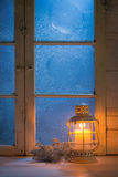 Frosted window at night with burning candle for Christmas Stock Image