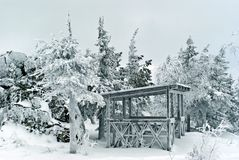Frosted wooden gazebo in the winter mountain forest. A wooden pavilion covered with hoarfrost in a picturesque frosty snow mountain forest near huge boulders Stock Photo
