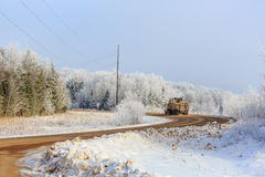 Frosted Woods and Logging Truck. A frost covered woods with a logging truck driving through it Royalty Free Stock Images