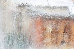Frostig modell på det glass vinterfönstret, blick till och med exponeringsglas royaltyfri foto