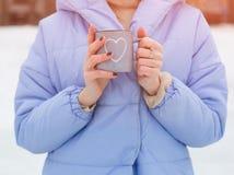 frostig morgonvinter Händerna för flicka` s rymmer en härlig varm kopp med en drink Del av kroppen Royaltyfri Fotografi