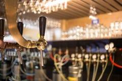 Frostigt exponeringsglas av ljust öl på stångräknaren Ölklapp arkivbild