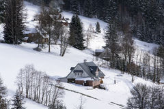 Frostigt snöig land med hus i en solig vinterdag Royaltyfria Bilder