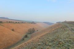 Frostigt vinterlandskap med en gräs- dal royaltyfria foton