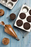 Frosting Cooled Chocolate Cupcakes Royalty Free Stock Photography
