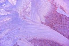 Frostmuster auf Fensterglas im Winter Bereiftes Glas-Beschaffenheit Blau und Purpur Stockfoto