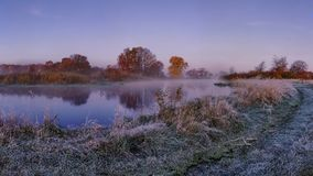 Frosty autumn morning landscape on river. Cold scenery with hoarfrost on the grass. Fall background Stock Photos