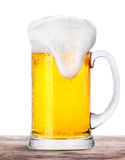 Frosty beer with foam isolated on wooden table Stock Photography