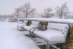 Frosty benches against a winter landscape in Utah. Empty benches covered with thick layer of snow on a park in Daybreak, Utah. A frosty snow covered winter stock photo