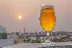 Frosty and detailed beer glass. With blurred background with sunset royalty free stock photo