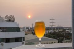 Frosty and detailed beer glass. With blurred background with sunset stock photos