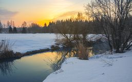Frosty foggy winter landscape with small forest river and rising sun. royalty free stock photography