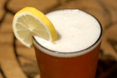 Frosty glass of beer with lemon slice Royalty Free Stock Images