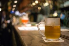 Frosty glass of light beer on the bar counter. Beer tap in Brussel Belgium. Glass of original dutch beer on bar table with blur pub background. Brussel Belgium Royalty Free Stock Photo