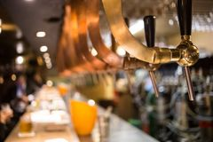 Frosty glass of light beer on the bar counter. Beer tap.  Royalty Free Stock Image