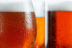 Frosty glasses of cool beer foam, covered with drops, closeup royalty free stock photo