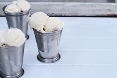 Melting Vanilla Ice Cream in Frosty Cups. Frosty metal cups filled with scoops of creamy vanilla ice cream Stock Photos