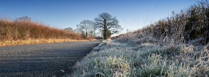Frosty morning in the Cotswolds, Gloucestershire, United Kingdom. Rural road with verge of frosted grass stock photography
