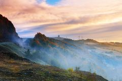 Cold morning fog with hot sunrise in conifer forest in mountains. Frosty morning fog in the mountains cold morning fog with hot sunrise in conifer forest in royalty free stock photo