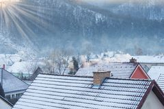 Frosty morning in a snowy village. Smoke on the roofs of houses. Heating coal and wood. Royalty Free Stock Images