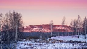 A frosty morning at sunrise. The sun illuminates the mountains. Snow everywhere. Frosty winter. The morning came.There`s snow everywhere. The mountains red from Stock Images