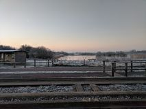 Frosty morning sunrise by train tracks with lake. Frosty sunrise over guided busway on early February morning in Fen Drayton, Cambridge, England with frozen lake royalty free stock images